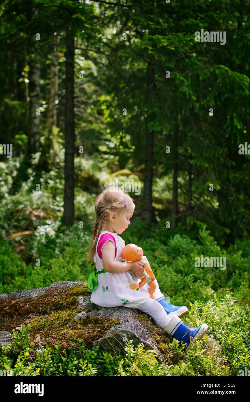 Finlandia, Paijat-Hame, lado-vista de chica (2-3) sentado con doll en roca Imagen De Stock