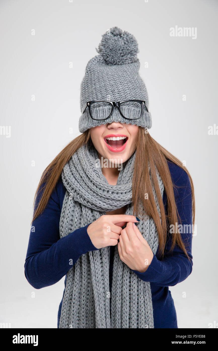 5ed381c149e3c Retrato de una mujer alegre y cubriendo sus ojos con sombrero aislado sobre  un fondo blanco
