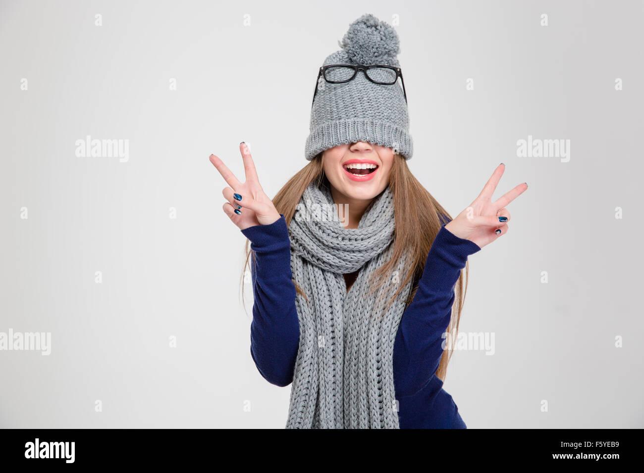 570e9ee646126 Retrato de una mujer alegre y cubriendo sus ojos con sombrero y mostrando  la paz signo aislado sobre un fondo blanco.