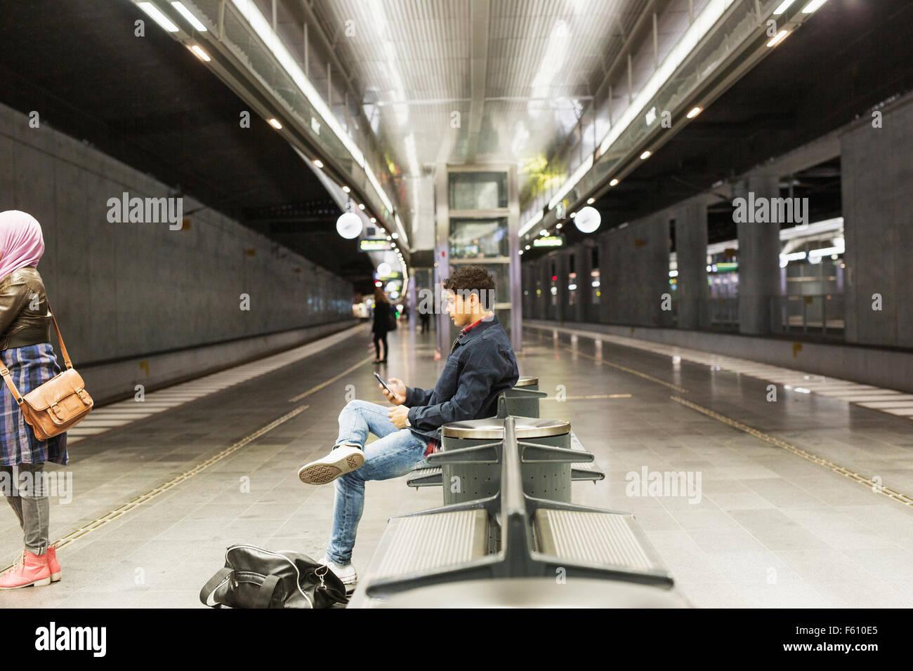 Vista lateral del hombre utilizando smart phone mientras está sentado en la plataforma de la estación Imagen De Stock
