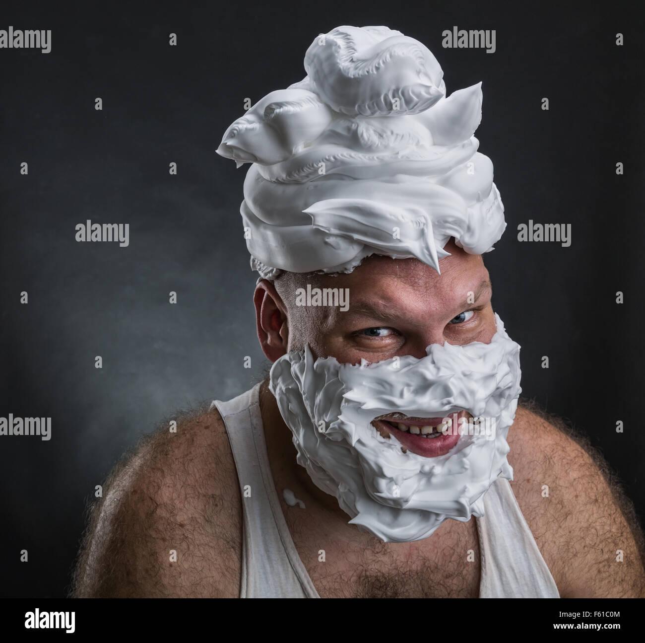Extraño hombre sonriente con espuma de afeitar en su rostro y en su cabeza sobre fondo gris Foto de stock