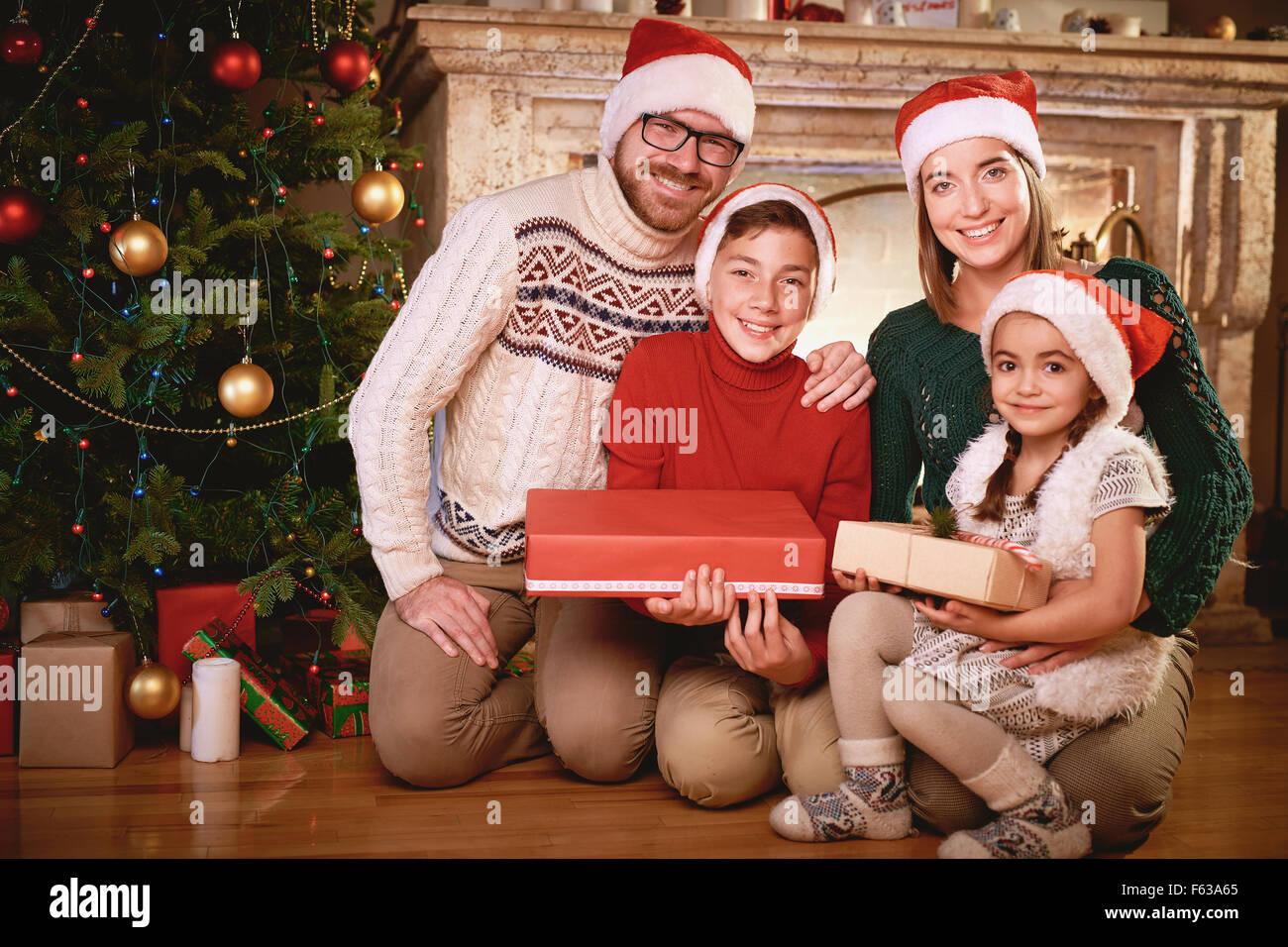 Familia Feliz en Santa caps mirando a la cámara por el árbol de Navidad Imagen De Stock