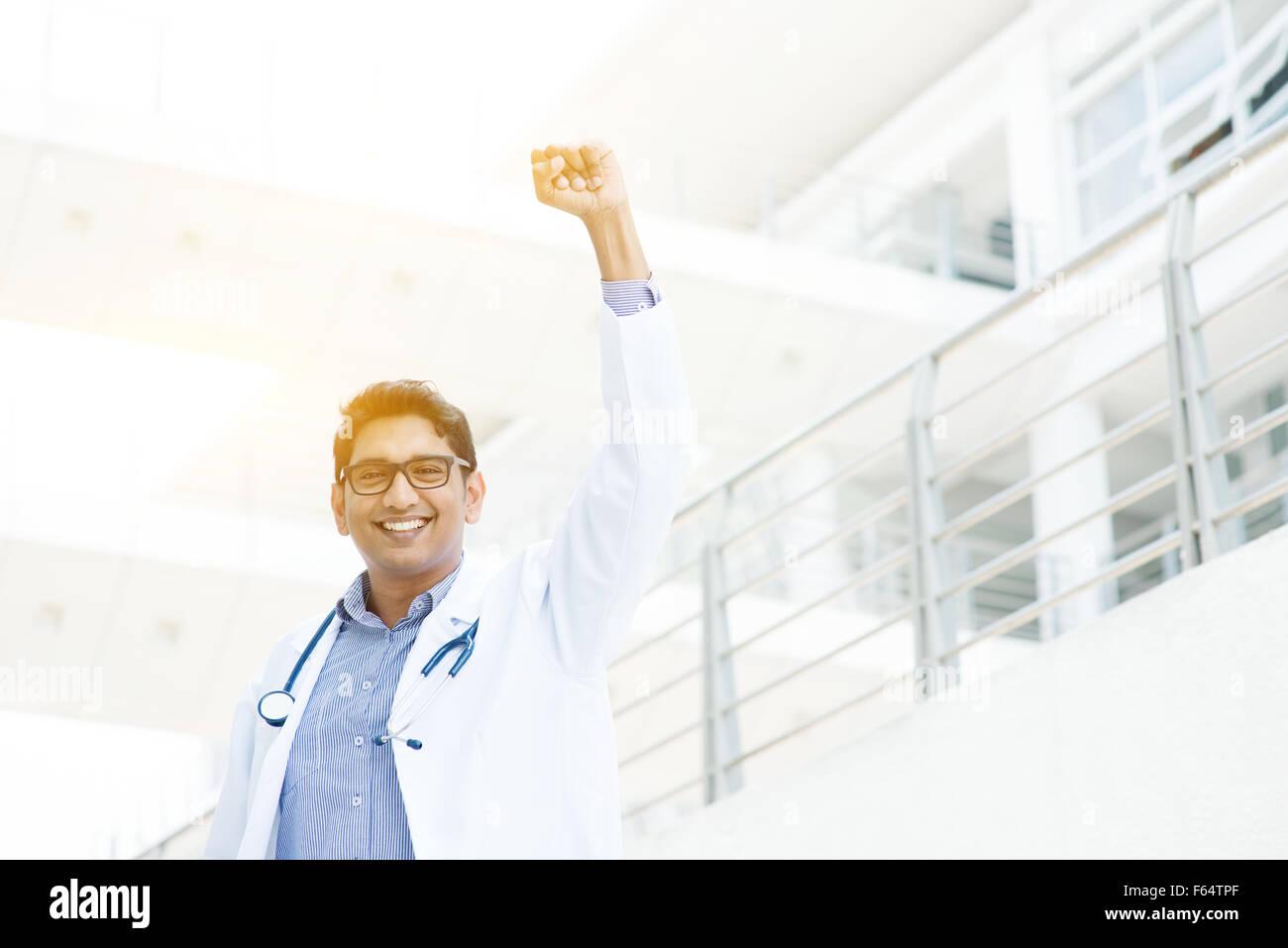 Exitoso médico indio asiático con el brazo celebrando su victoria, el edificio del hospital como fondo. Foto de stock