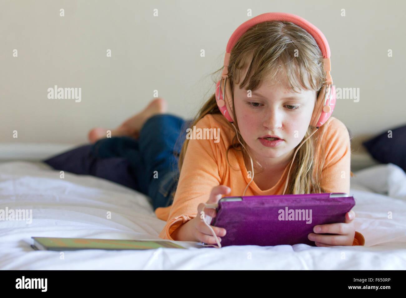 Chica trabajando en el iPad mini con auriculares Imagen De Stock