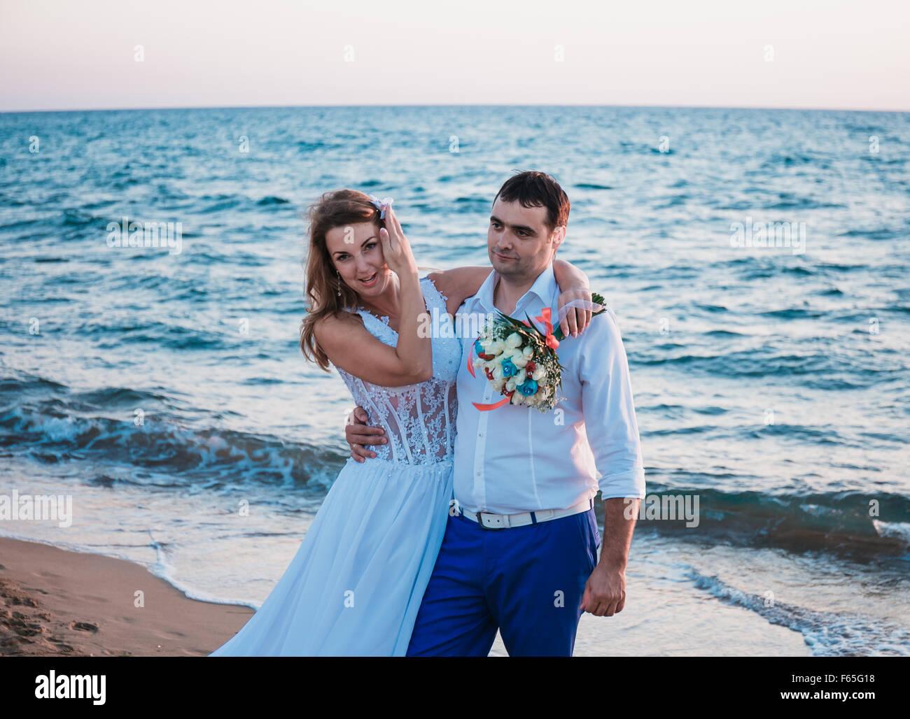 Los recién casados caminando sobre una playa Imagen De Stock