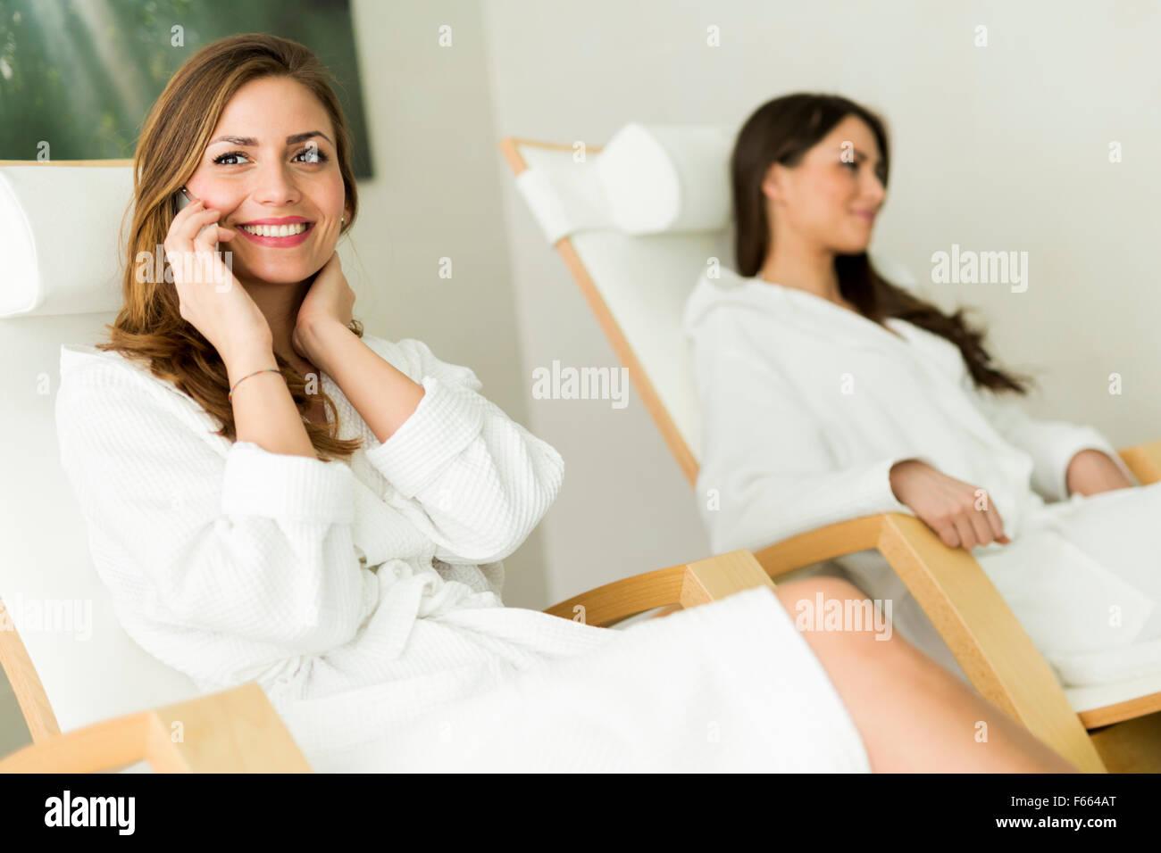 Joven y bella mujer de relax en un spa vistiendo ropas y hablar por teléfono Imagen De Stock