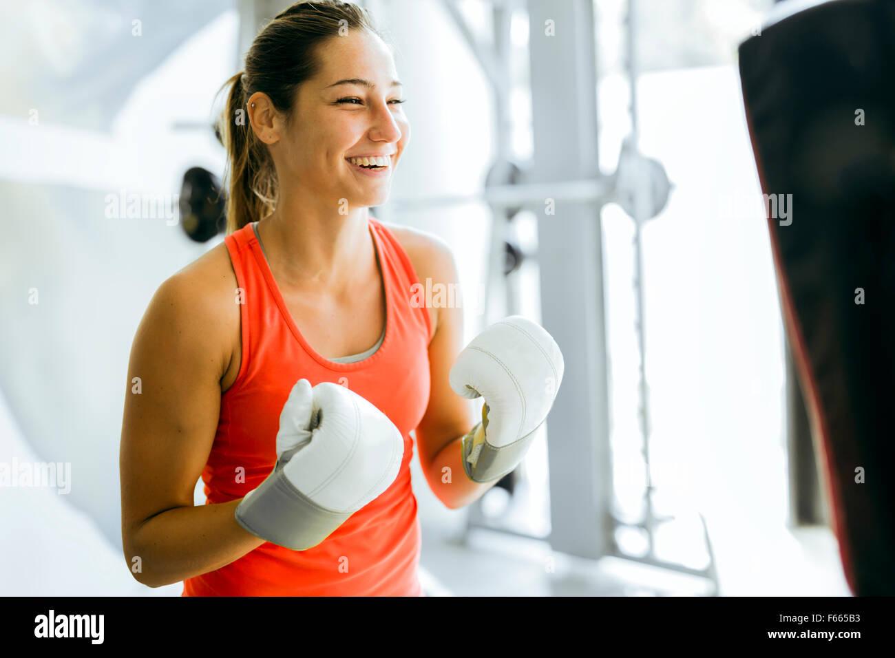 Mujer joven y entrenamiento de boxeo en un gimnasio Imagen De Stock