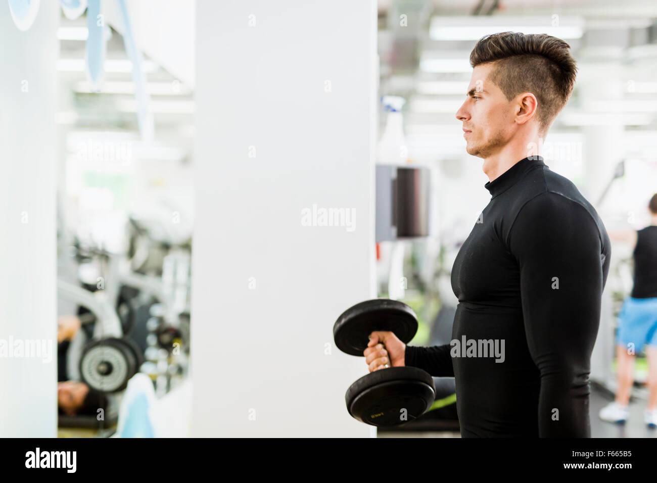Joven apuesto hombre trabajando en un gimnasio y levantar pesas Imagen De Stock