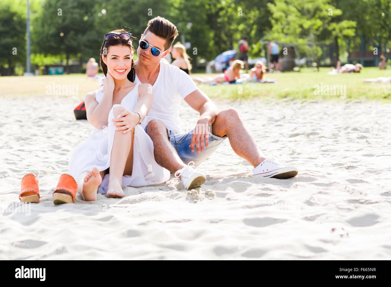 Pareja joven en el amor romántico sentado en una playa de arena y sonriente Imagen De Stock