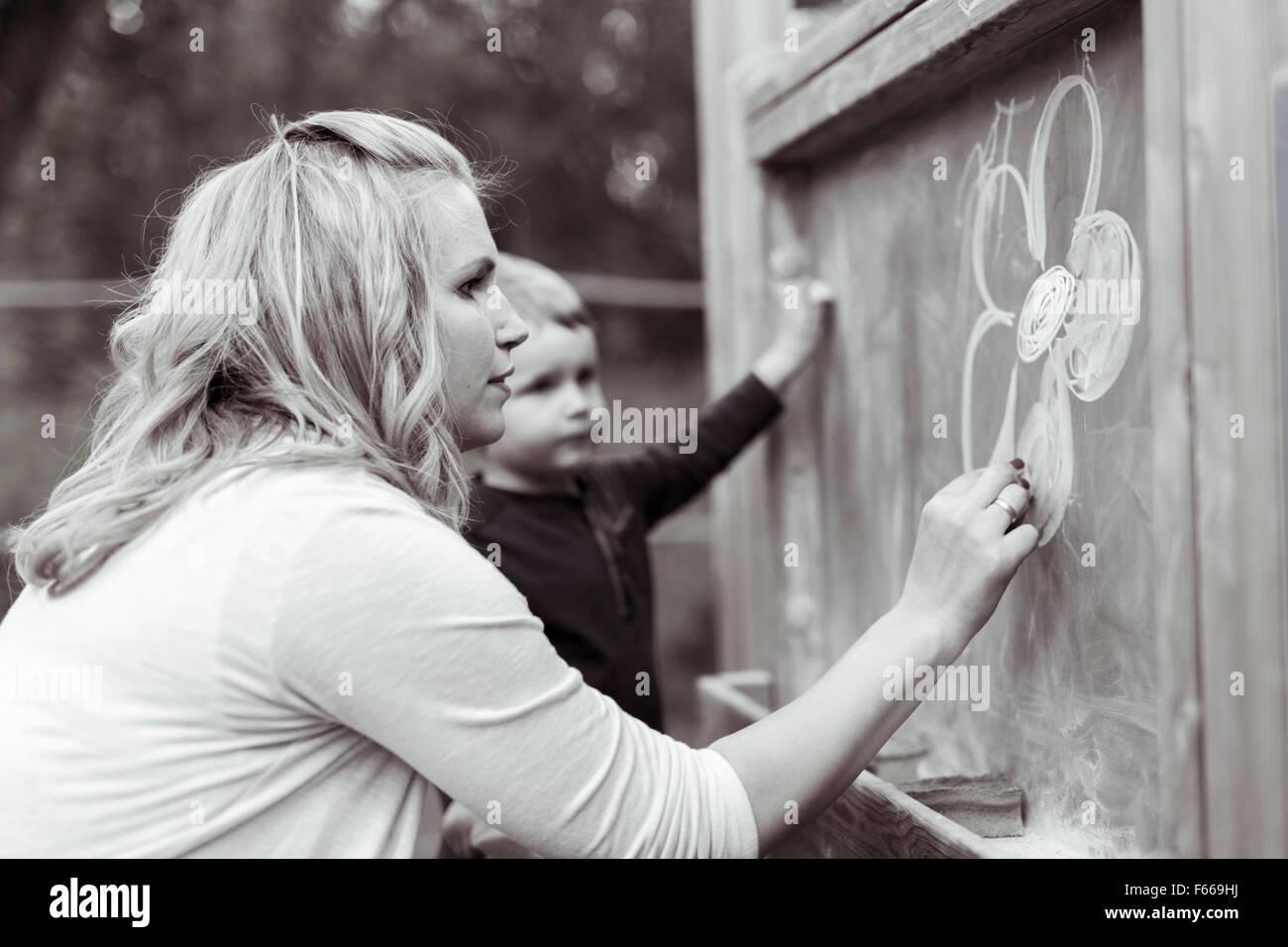 Madre e hijo hermoso dibujo en pizarra con tiza Imagen De Stock