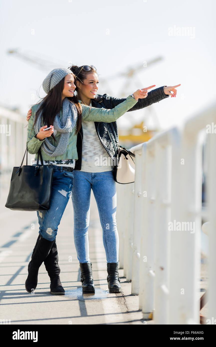 Dos jóvenes y bellas mujeres mirando por encima de una valla de dock y apuntando a una dirección Imagen De Stock