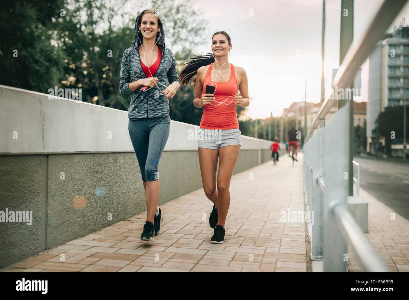 Hermoso paisaje de dos mujeres deportistas realizando sus actividades al aire libre en la ciudad en el atardecer Imagen De Stock