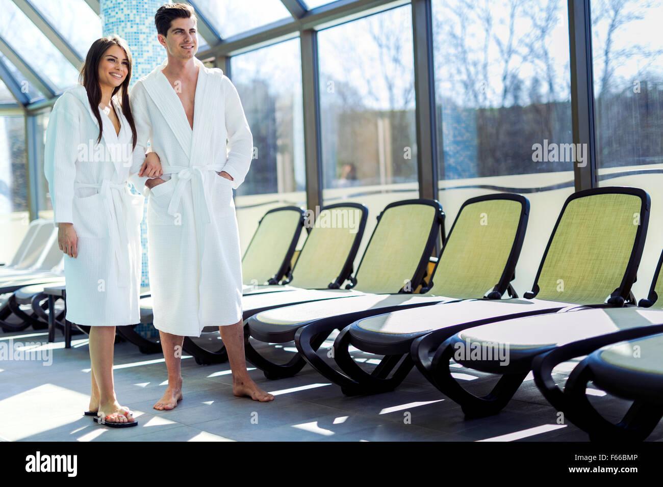Pareja de amor de pie junto a una piscina en un manto y relajante Imagen De Stock