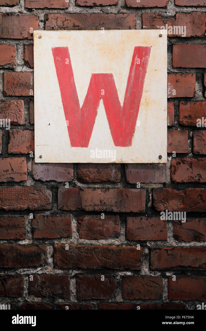 Viejo cartel con la letra W en una pared de ladrillo. Foto de stock
