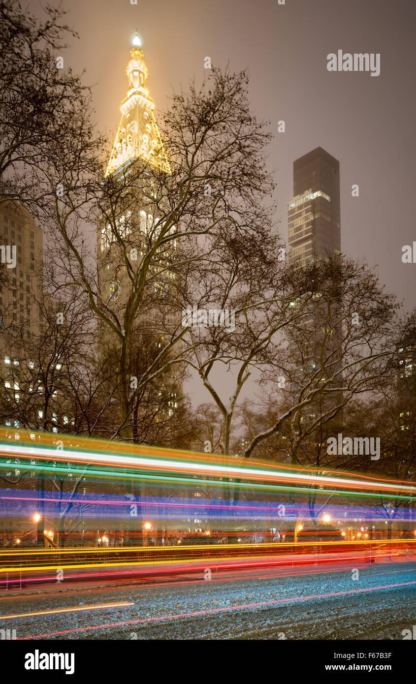 Los rascacielos durante Tormenta en Madison Square Park. Las luces traseras se encienden coche nieve en 5th Avenue. Imagen De Stock