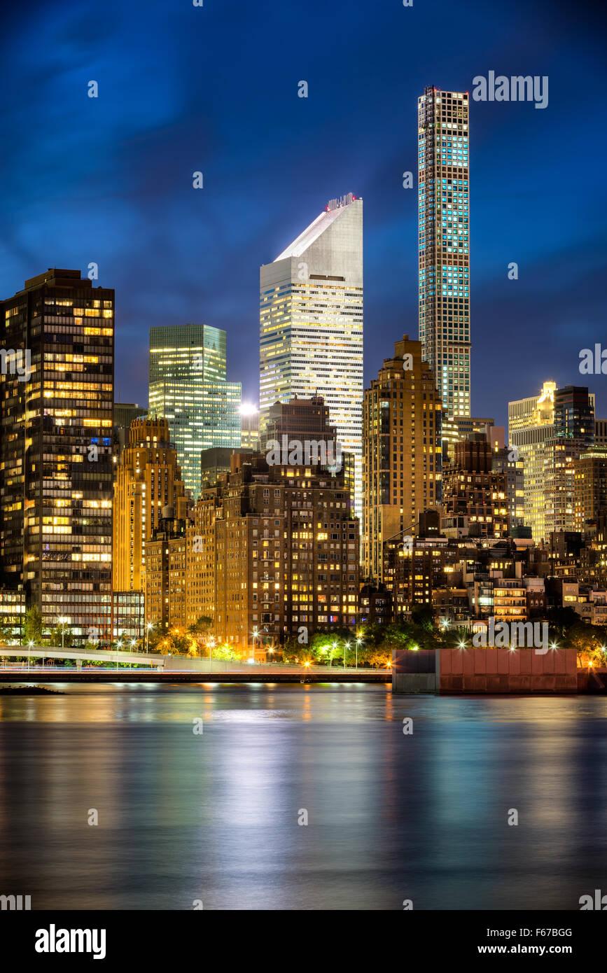 Los rascacielos de Midtown Manhattan iluminada y las luces de la ciudad se refleja en el East River en penumbra. Imagen De Stock
