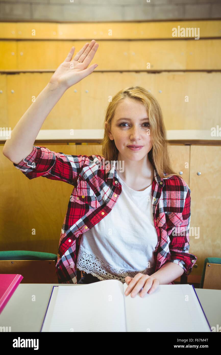 Estudiante rubia levantando la mano durante la clase Imagen De Stock
