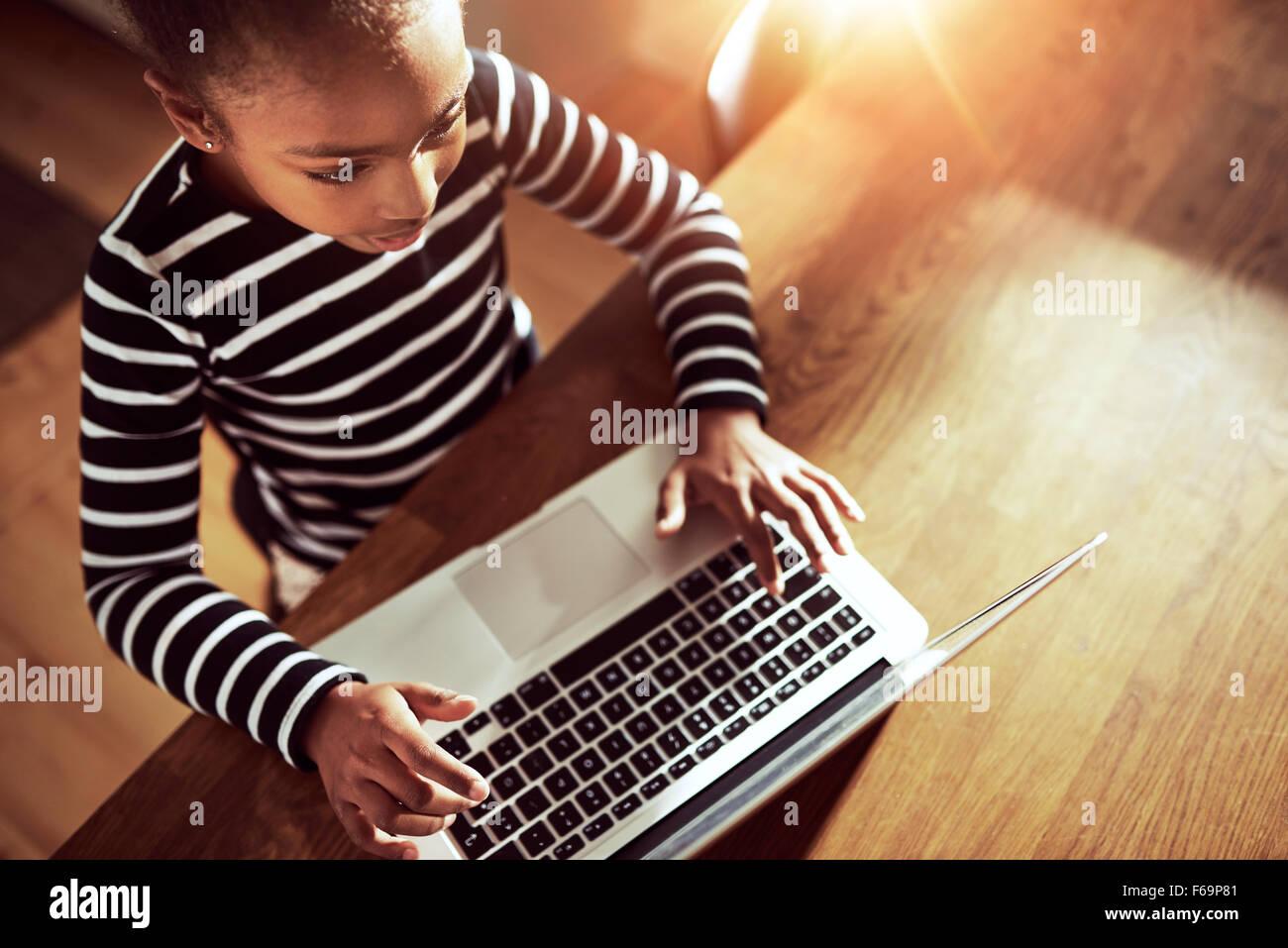 Joven negro étnico chica sentada en la mesa del comedor en casa escribiendo en un ordenador portátil, Imagen De Stock