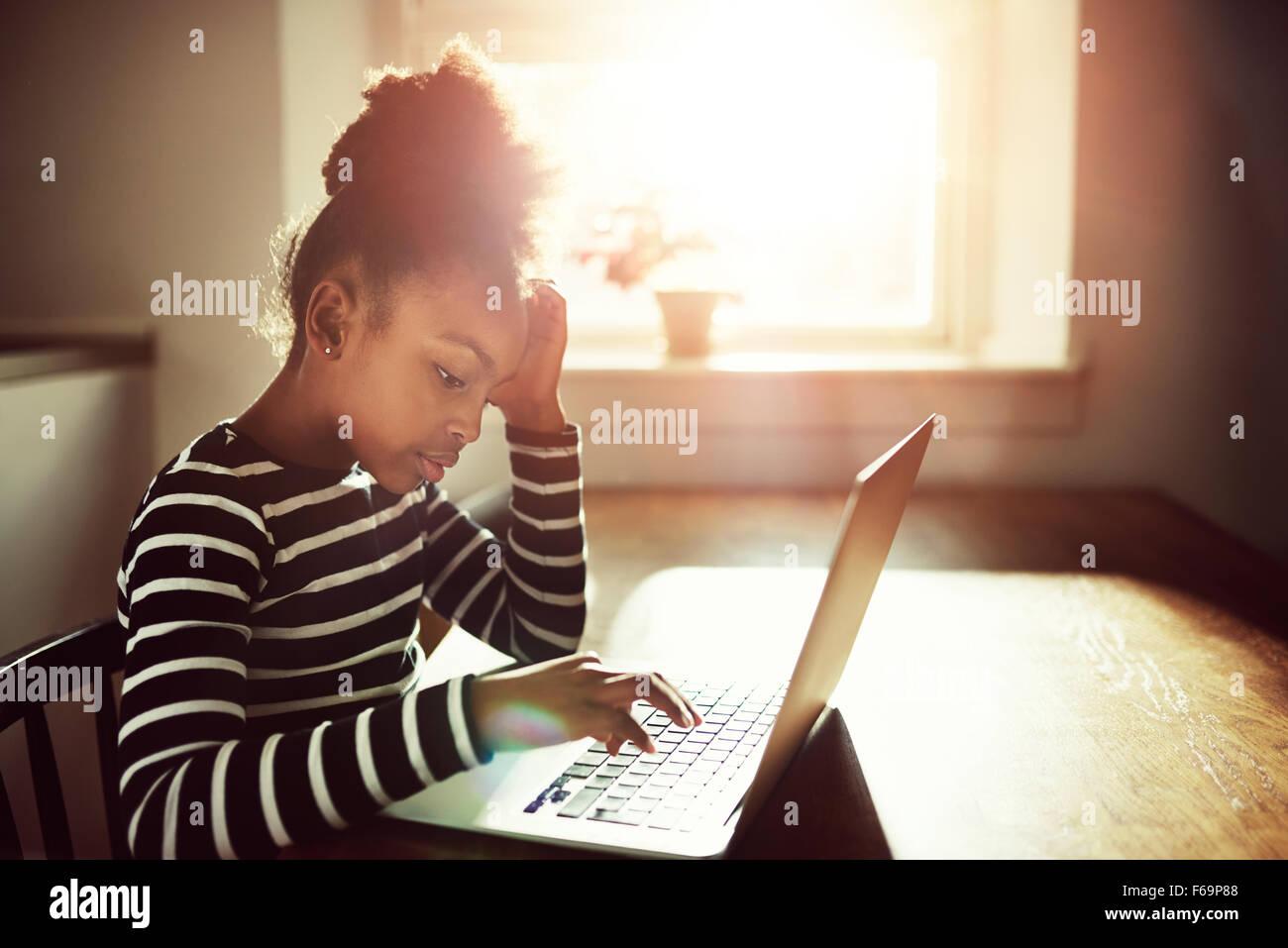 Joven negro niña trabajando en sus deberes en casa escribiendo información en un ordenador portátil, vista lateral contra un sol brillante resplandor Foto de stock