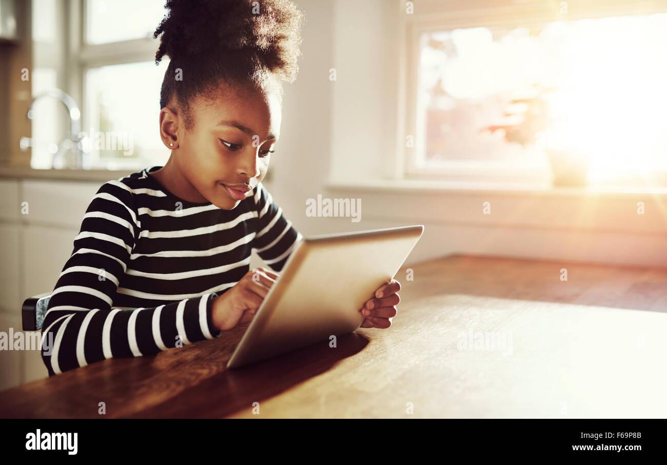 Joven negro chica con un peinado afro divertido sentarse a una mesa en casa navegando por internet en un ordenador Imagen De Stock