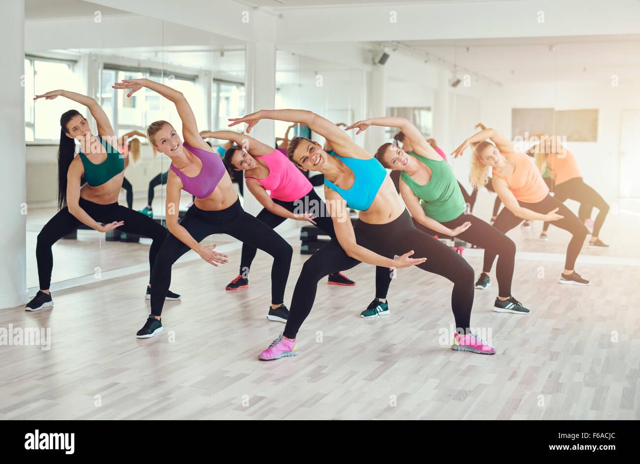 Clase de aeróbicos en el gimnasio con un grupo de atractivas mujeres jóvenes fit en coloridos sportswear Imagen De Stock