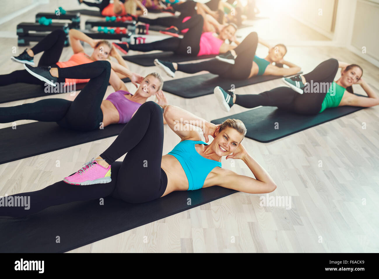 Grupo de colocar mujeres jóvenes sanos en un gimnasio vistiendo coloridos sportswear trabajando en una clase Imagen De Stock
