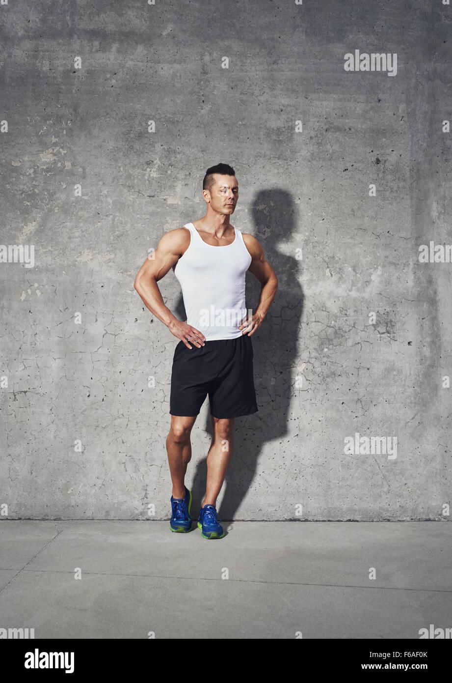 Full body fitness retrato del hombre musculoso, de pie con ambas manos en su cintura mirando lejos Imagen De Stock