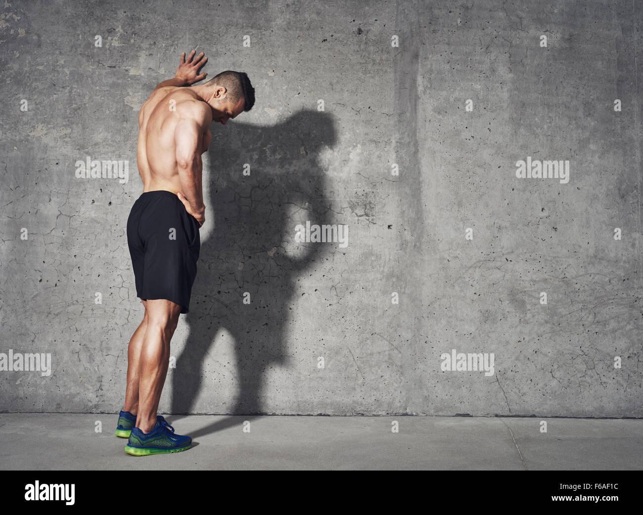 Joven descansando después de un entrenamiento activo mientras está de pie contra la pared gris con copia Imagen De Stock
