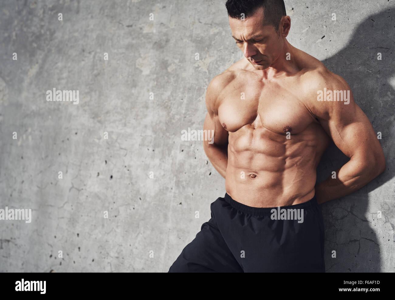 Cerrar imagen de macho en shorts relajante después de entrenar sobre fondo gris. Musculoso cuerpo masculino Imagen De Stock