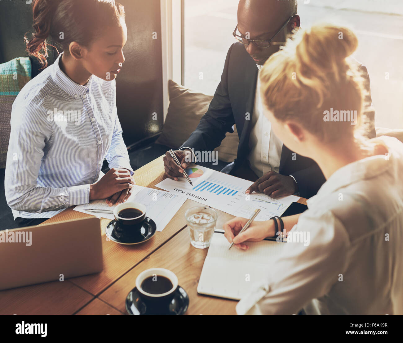 Gente de negocios discutiendo las tablas y gráficos que muestran los resultados de su exitoso trabajo en equipo, Foto de stock