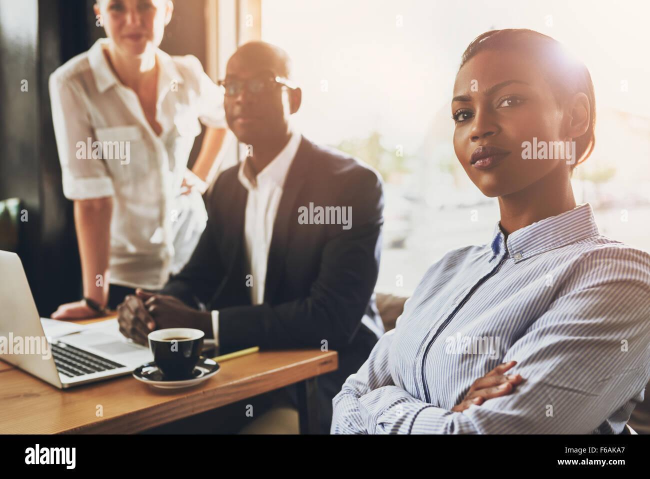 Seguro joven negro mujer de negocios sentada en frente de otras personas de negocios Imagen De Stock