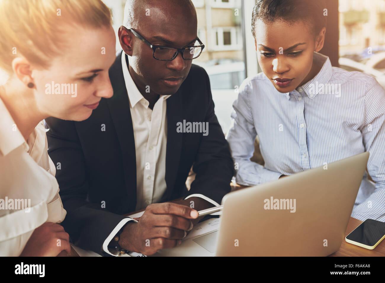 Varios negocios étnicos personas trabajando en la oficina sentado delante de un ordenador portátil, negro mujer de negocios, mujer de negocios blanco Foto de stock