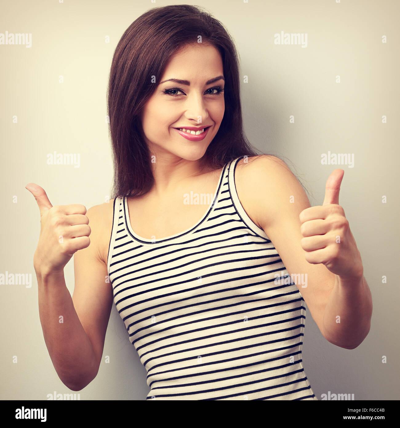 Feliz éxito casual joven mujer mostrando pulgar arriba firmar. Retrato de tonos Vintage Imagen De Stock