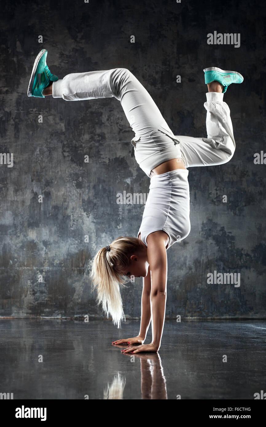 Joven bailarina moderna de pie en las manos. Muro de piedra en el fondo. Imagen De Stock