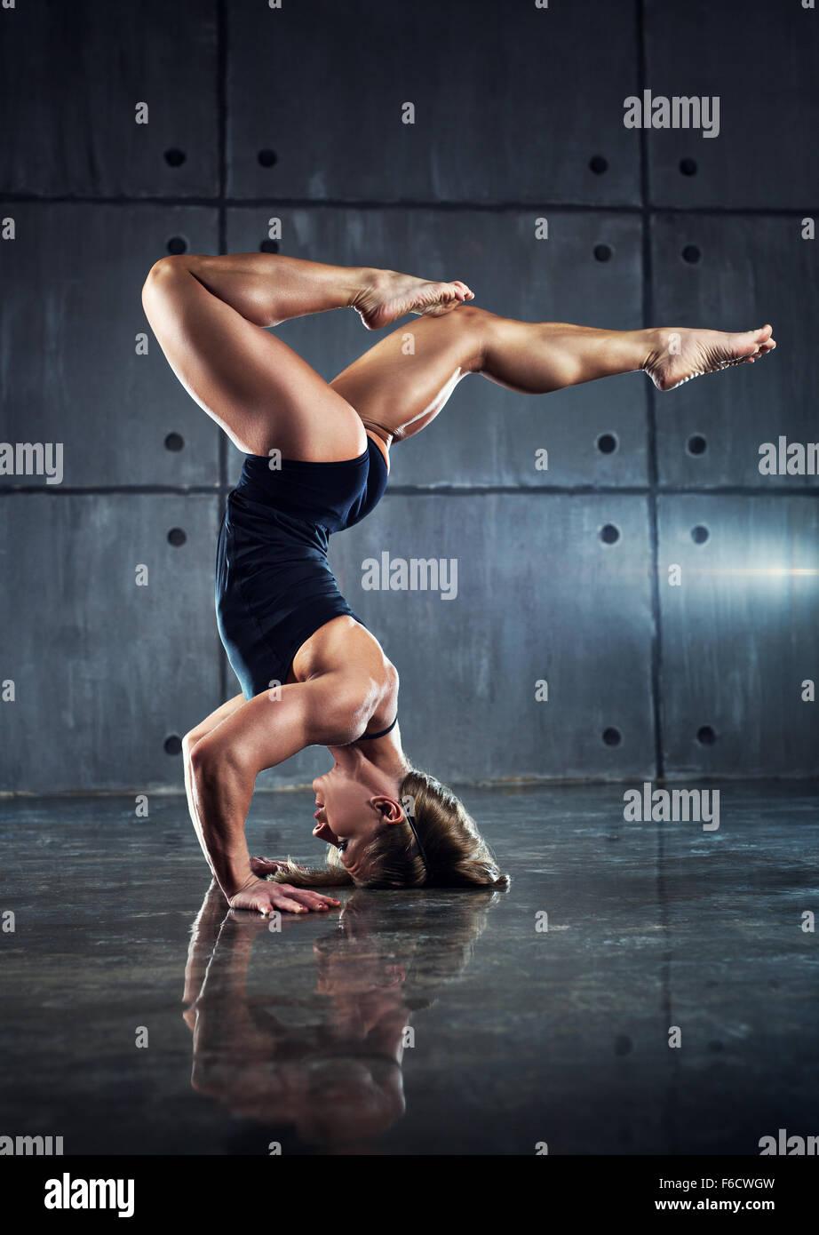 Mujer fuerte y permanente culturista boca abajo en la pared de fondo. Imagen De Stock