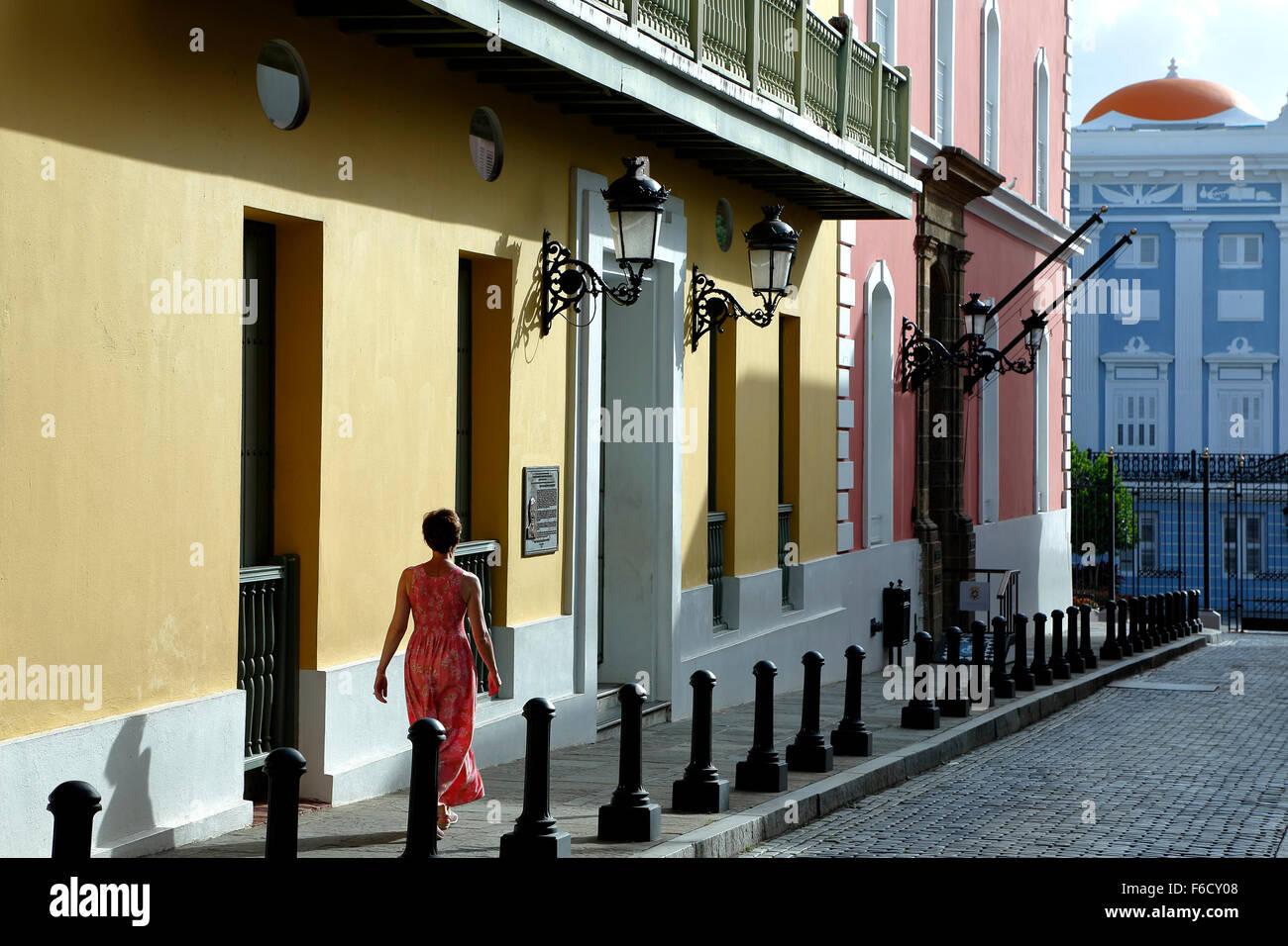 Mujer y coloridas fachadas coloniales españolas (Oficina Estatal de Preservación Histórica), Calle Fortaleza, el Viejo San Juan, Puerto Rico Foto de stock