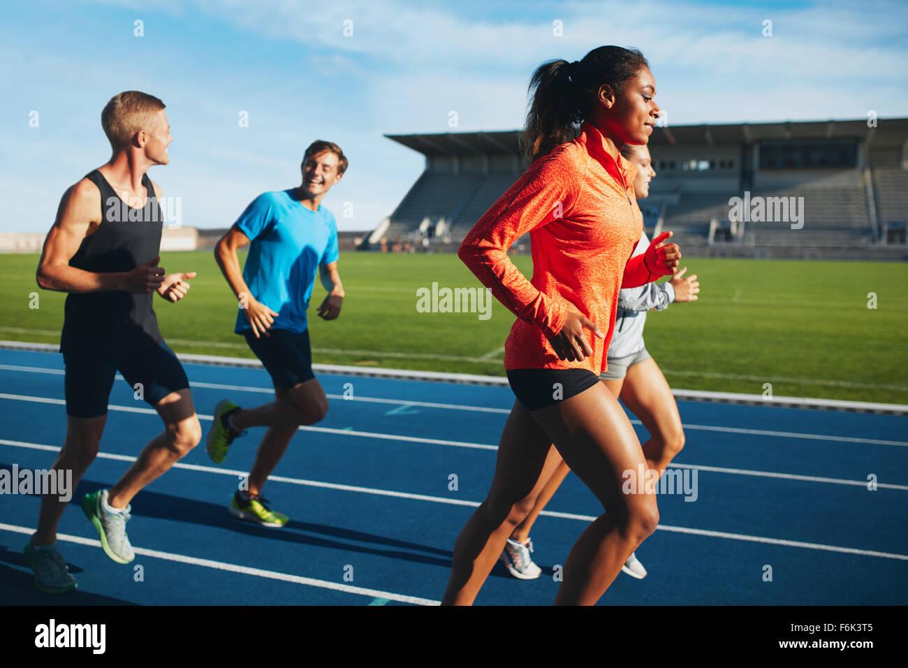 d77566b9f8 Colocar hombres y mujeres corriendo en una pista de carreras. Atletas  multirracial practicando en la pista de carreras en el estadio.