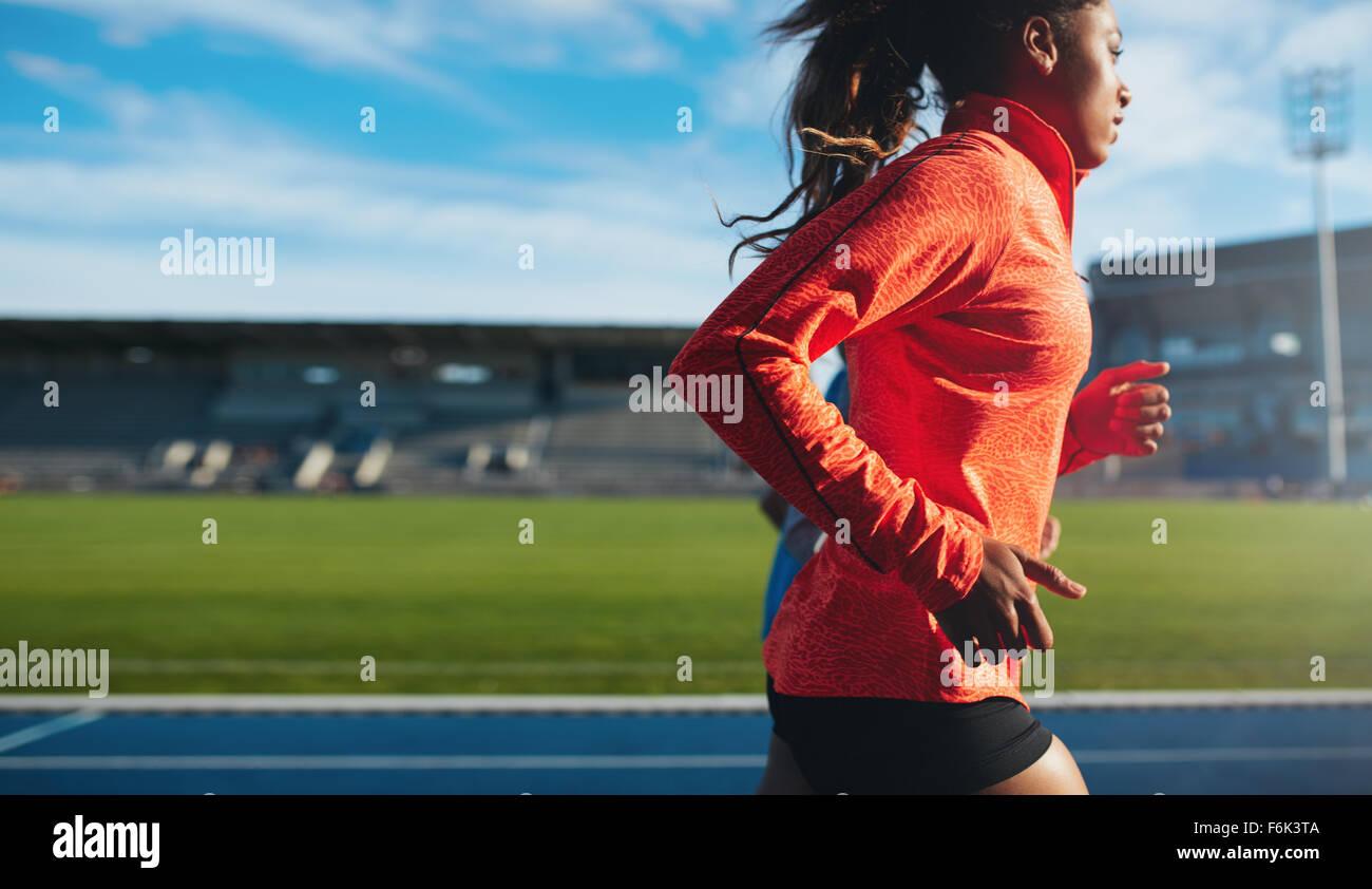 Vista lateral del monte joven en ejecución. Formación de la atleta femenina africana en pista en el estadio Imagen De Stock