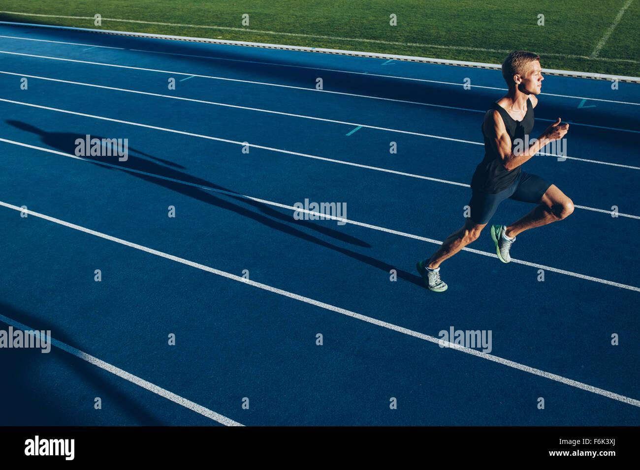 Foto de joven profesional sprinter corriendo en pista. Runner practicando su corrida en la pista de atletismo. Imagen De Stock