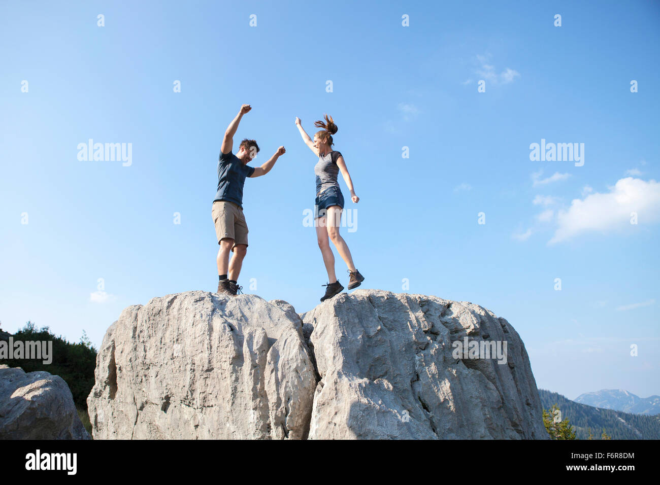 Pareja joven aclamando en el pico de la montaña Imagen De Stock