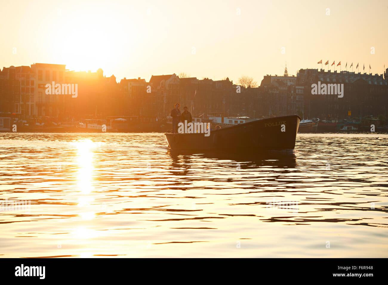 La gente durante el viaje en bote en un canal de Amsterdam al atardecer. Imagen De Stock