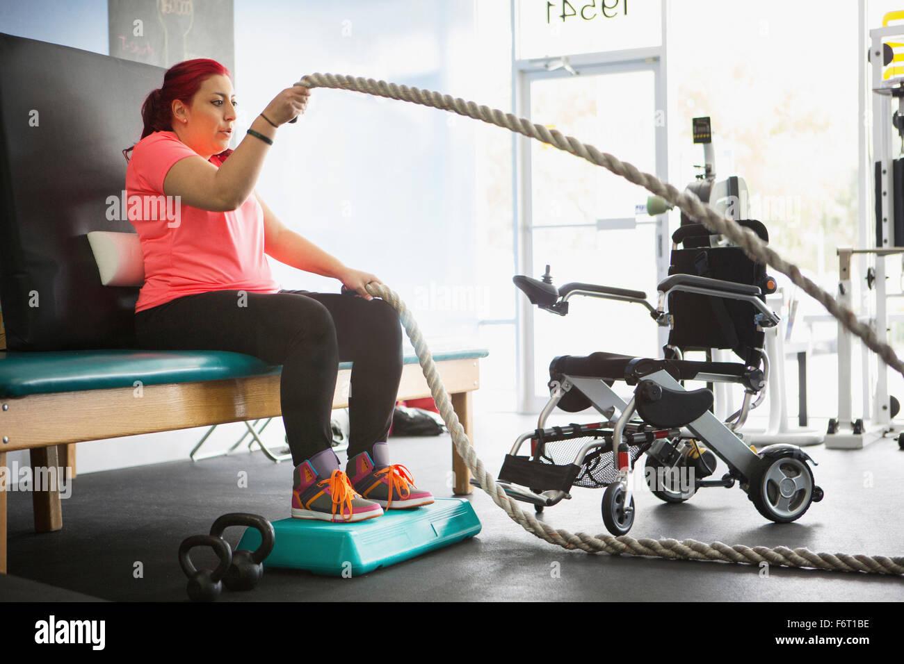 Mujer discapacitada haciendo terapia física en el gimnasio Foto de stock