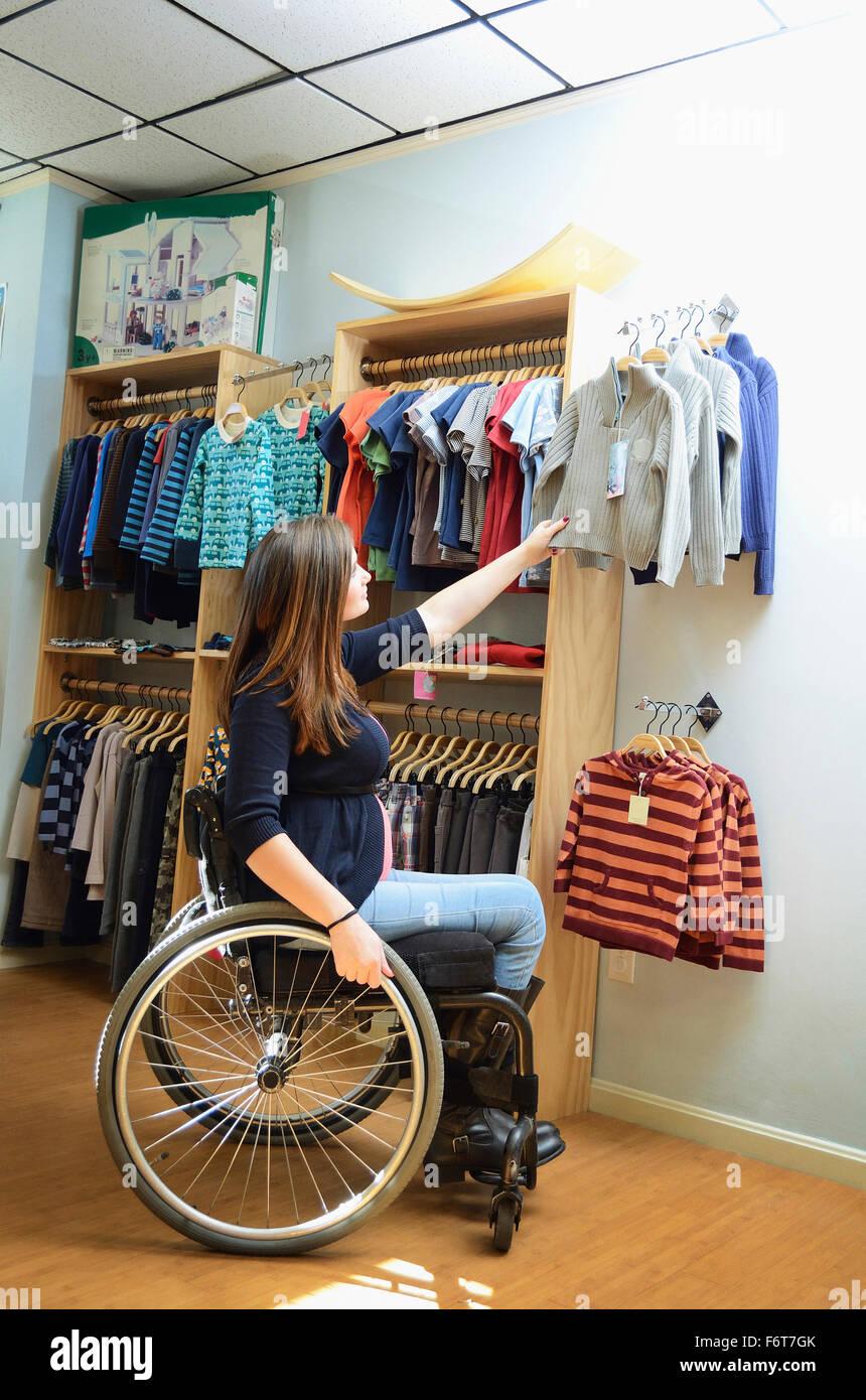 Mujer embarazada parapléjico en silla de ruedas compras en tienda de bebé Foto de stock