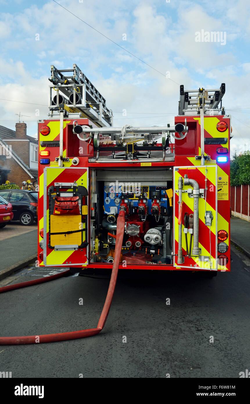 Una nueva totalmente equipada de bomberos extinguir un incendio Foto de stock