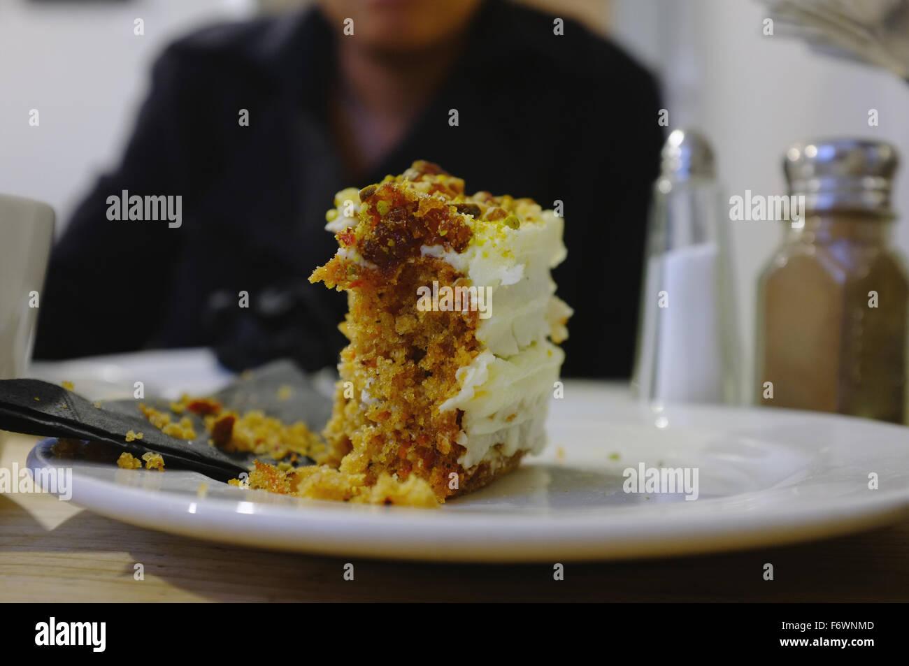 Una mitad comido trozo de pastel de zanahoria en una placa en el interior de un café en Brighton. Imagen De Stock