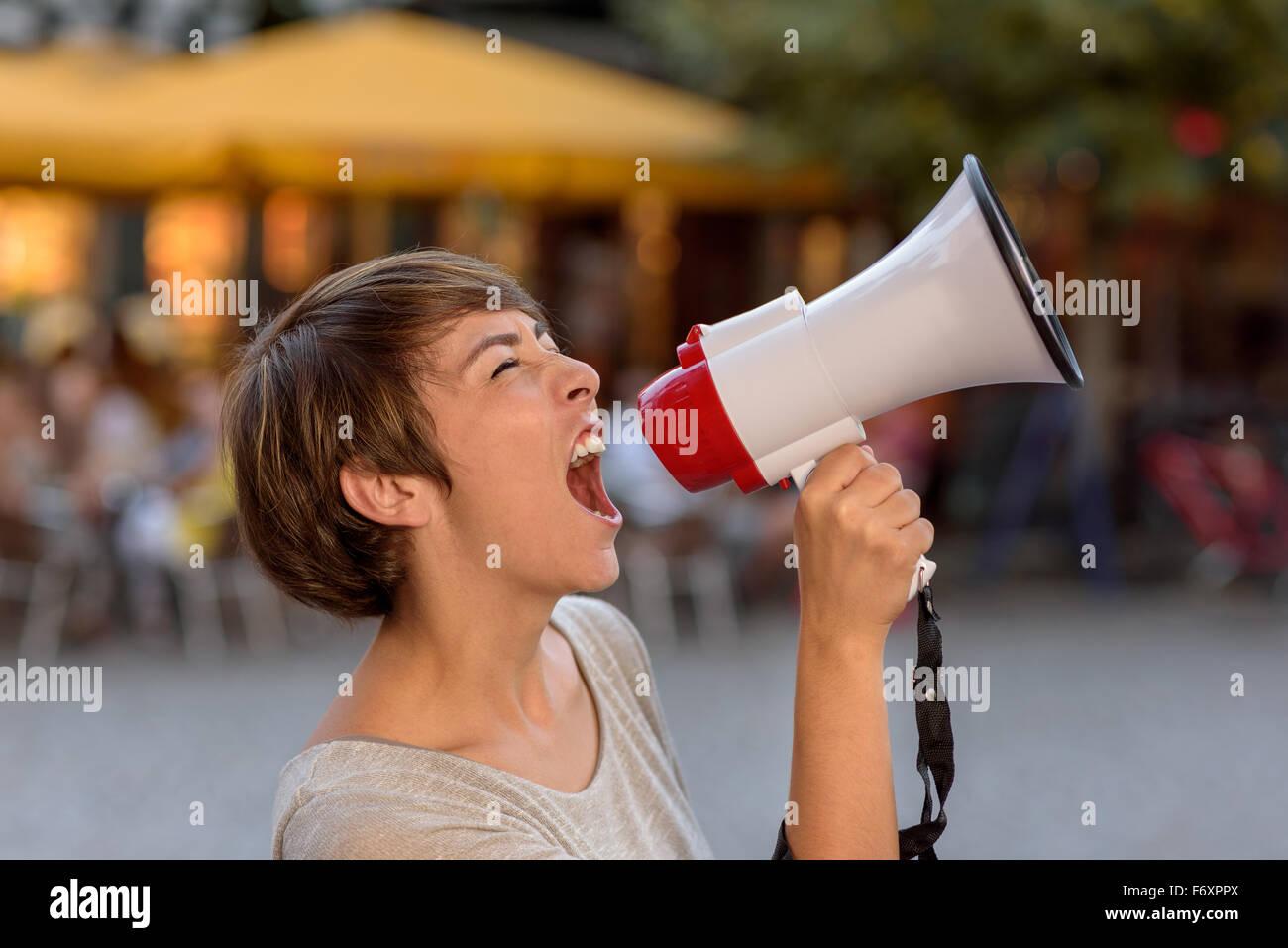 Joven enojado gritando en un megáfono como ella se sitúa en una calle urbana, ventilando sus frustraciones durante Foto de stock