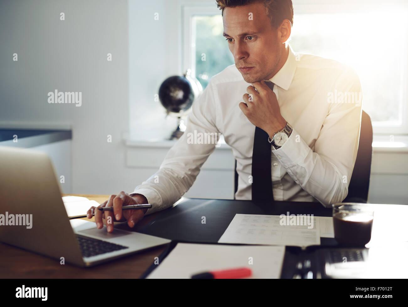 Hombre de negocios sentado en su mesa de trabajo en un ordenador y mirando concentrado Imagen De Stock