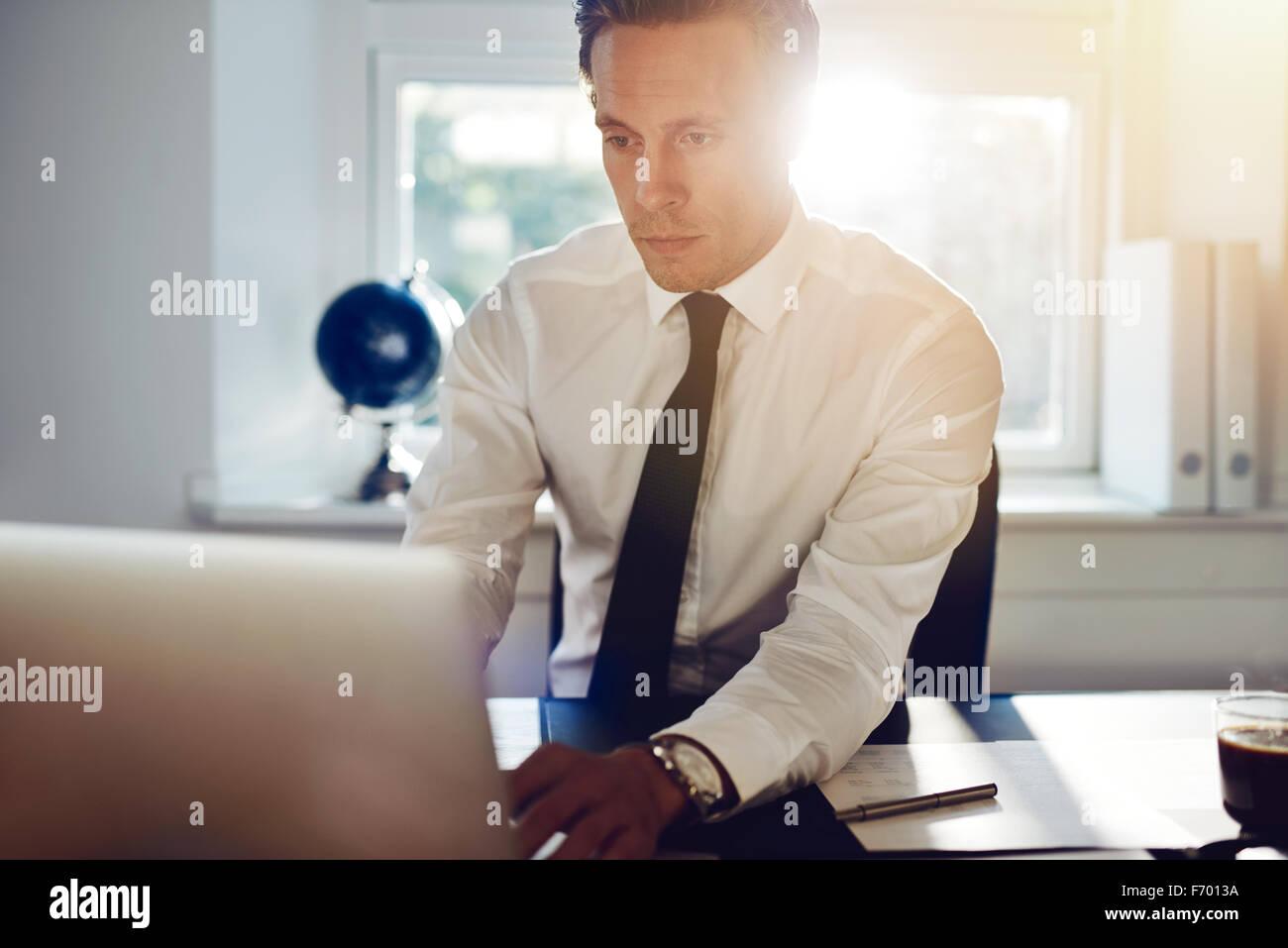 Blanco joven hombre de negocios trabajando en equipo sentado en su escritorio Imagen De Stock