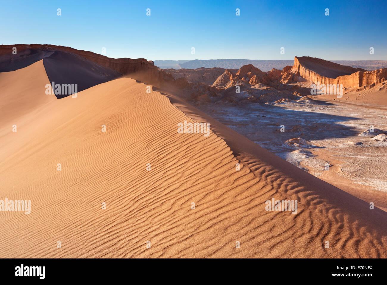 Una alta duna de arena y formaciones rocosas distantes. Fotografiado en el Valle de la Luna en el desierto de Atacama, Imagen De Stock