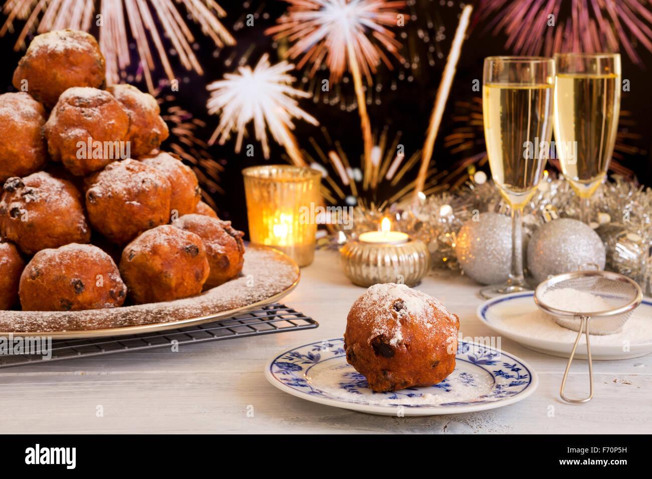 'Oliebollen', repostería tradicional holandés para la Víspera del Año Nuevo. Con champán y fuegos artificiales en el fondo. Foto de stock